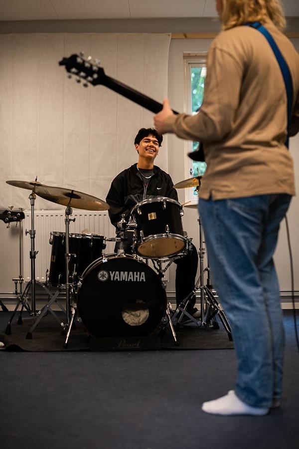 musikstuderande spelar trummor och gitarr